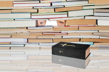 Holy Book against the backdrop of numerous books and people. Stock Photo
