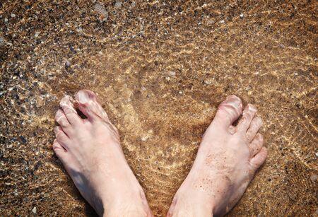 Bare feet in sea water