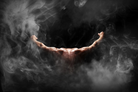 Image of muscles of the back on a black background in to smoke  photo