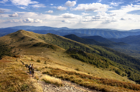 Green peaks in the Bieszczady mountains in during the late afternoon in summer and people walking by path going through the peaks Stock Photo