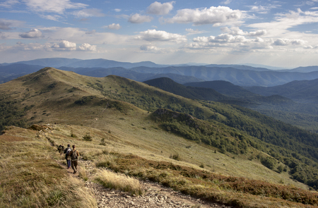 Green peaks in the Bieszczady mountains in during the late afternoon in summer and path going through the peaks