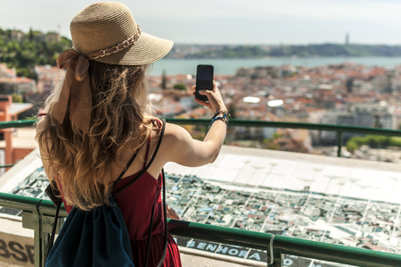 Woman is using a smartphone and looking at a panoramic view on the city of Lisbon in Portugal