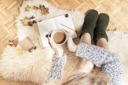 Coziness at home, girl doing hygge with book and warm blanket