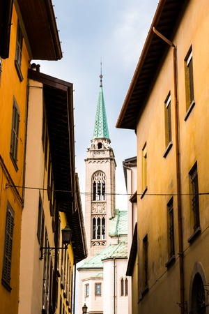 The medieval Italian church is visible in a narrow street, Lovere, Italy