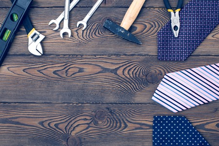 Happy fathers day concept with tie, gift and tools empty notebook on a wooden table top view in flat lay style. Stock Photo