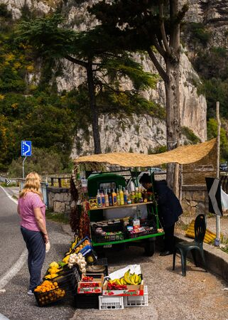 Italy, the region of Campania, Amalfi - April 11,2017: An elderly woman sells vegetables and drinks from a small car on a road in the mountains.