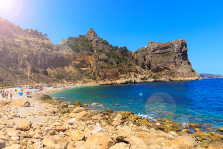 Beautiful view of beach in a bay with turquoise water in the sun, La playa Moraig in Cumbre del Sol, Spain