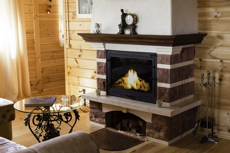 Warm cozy fireplace with real wood burning in it. Cozy winter concept. Christmas and travel background.