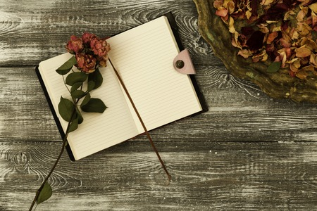 Top view of vintage tray with petals of dried rose flowers and a diary or notebook and dried rose flower on a gray wooden table. Flat design. Copy space