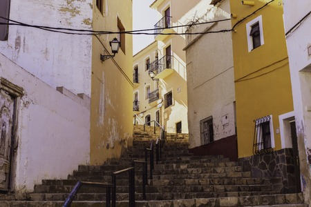 Narrow street in the form of a staircase with traditional houses with peeling plaster of the old city of Finestrat Spain.