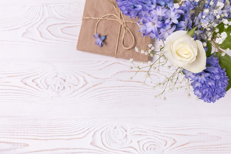 A gift box wrapped in craft paper and blue hyacinth flowers, white roses on a white table top. Flat lay. Copy space for text.