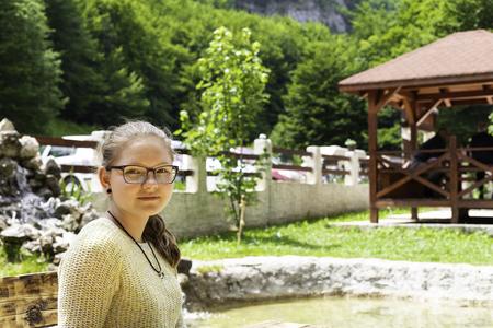 Beautiful smiling teenage girl wearing glasses in a sweatshirt sitting against a green summer park 版權商用圖片
