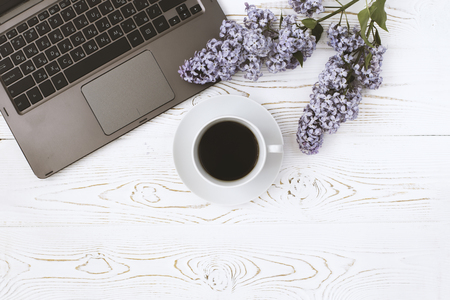 Top view of a computer and a cup of coffee and lilac flowers on a white wooden table. Place for text