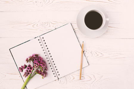 Top view of a diary or notebook, pencil and cup of coffee and a purple flower on a white wooden table. Flat design Stock Photo