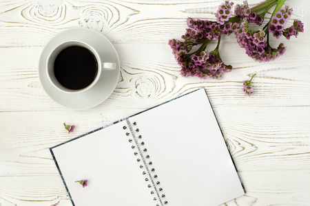Top view of a diary or notebook and coffee and a purple flower on a white wooden table. Flat design.