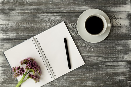 Blank diary or notebook with a spring, a pencil and a cup of coffee and pink flower on a gray shabby wooden table. Flat design.