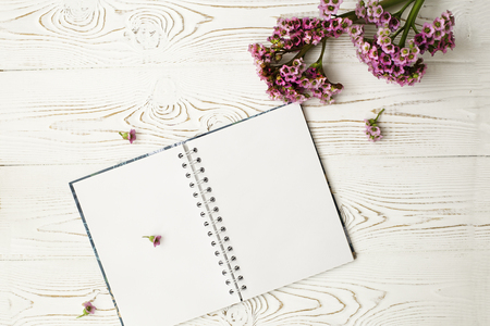Blank diary for your text and pink flower on a white wooden table. Flat design. Stock Photo