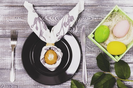 Top view of an easter egg wrapped in a napkin in the shape of rabbit ears on a black plate and cutlery, colorful Easter eggs in a wooden box on a wooden gray table Фото со стока