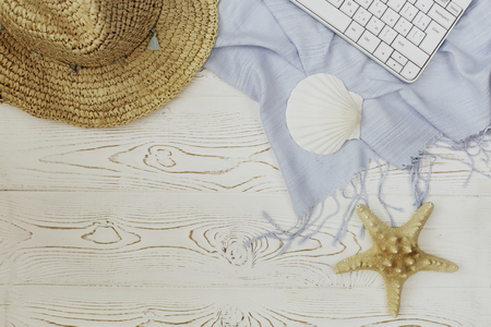 Women's straw hat, blue stole, keyboard, seashell and starfish on white wooden background and place for text. Summer vacation concept of flat lay