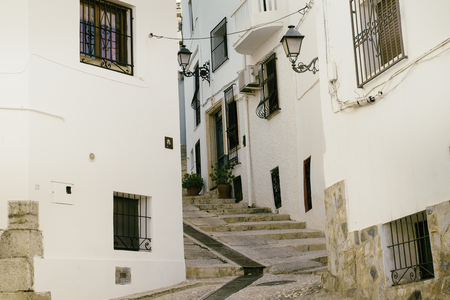 Beautiful narrow street in the old town with white houses and a cobblestone road. Altea, Spain. Reklamní fotografie - 124869085