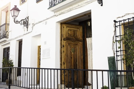 Beautiful door with carvings and forged lantern on the wall of a white house on the street of the old town of Althea, Spain