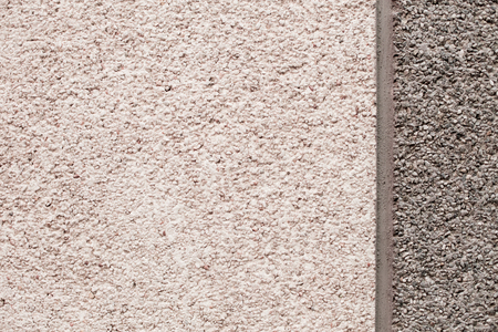 Stone wall, smooth surface, asphalt crumb, bitumen background. The trim is in beige and gray tones, separated by a cement vertical stripe.