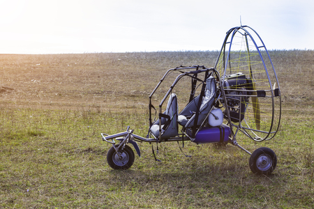 Closeup of moto paraglider on the field.