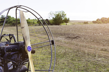 Closeup of a propeller with a motor-paraglider motor against the background of a field.