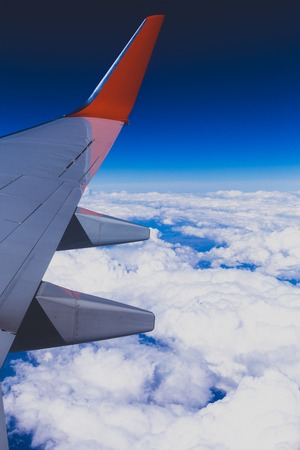 Aerial view of cloud blue sky and plane wing view through the airplane window. Copy space