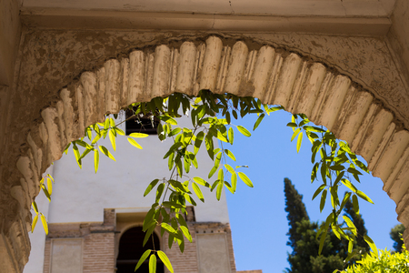 Details of the arch of the Generalife courtyard with its famous fountain and garden. Alhambra de Granada complex.