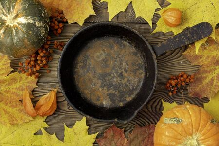 Autumn table for Thanksgiving dinner. Top view of maple leaf on a empty pan and fallen colored leaves on a wooden table. The concept of autumn food.
