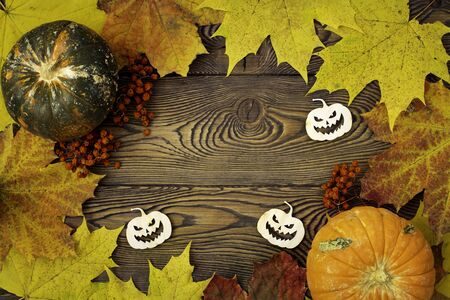 Halloween background with pumpkins, autumn maple leaves and spooky pumpkins carved in wood. Flat lay. Zdjęcie Seryjne