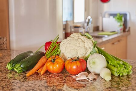 Ingredients for Italian vegetable soup. Celery, tomato, onions and carrots, cauliflower and garlic, zucchini on a table in the kitchen