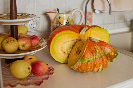 Beautiful large pumpkin with large seeds and red apples on a fruit stand on a table in the kitchen.