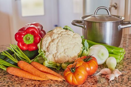 Ingredients for Italian vegetable soup. Celery, tomatoes, onions and carrots, cauliflower and garlic, zucchini and tureen on a stone table. Stock Photo