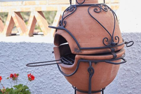 Clay burner with a wrought iron pattern on the terrace and balcony Banque d'images - 138012319
