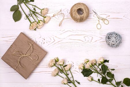 Gift box wrapped in kraft paper and flower, twine and scissors on a white wooden background from above. Flat lay styling.