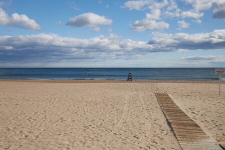 Lonely sandy beach with a lifeguard and a boardwalk to the sea on the Costa Blanca Spain.
