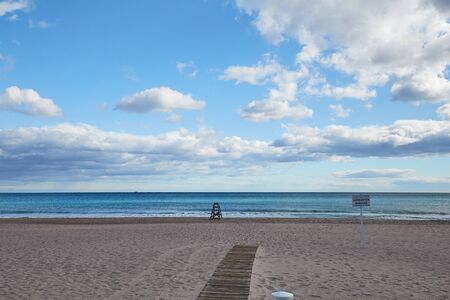 Lonely sandy beach with a lifeguard and a boardwalk to the sea on the Costa Blanca Spain. Standard-Bild