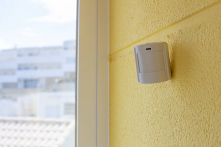 Motion sensor or detector for security system on a yellow wall by the window, indoors. Place for text. Stock Photo