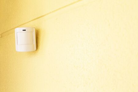 Motion sensor or detector for security system on a yellow wall indoors. Place for text.