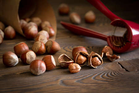 Hazelnuts with a red nutcracker on a wooden board. Nuts in craft paper, dark photo, selective focus.