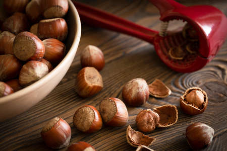 Hazelnuts in a bowl with a red nutcracker on a wooden table, nutshell, dark photo, selective focus.