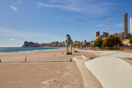 Benidorm, Alicante, Spain - November 27, 2019: people walk along the fantastic modern promenade of Poniente with views of skyscrapers, palm trees, rocks.