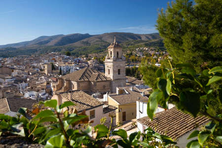 Caravaca, Spain - November 17, 2017: panorama of the city of Caravaca de la Cruz and conifers in the foreground, a place of pilgrimage near Murcia in Spain