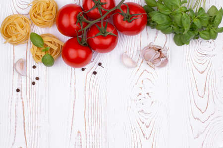 Top view raw tagliatelle pasta with fresh basil, garlic and tomatoes on a rustic white table, flat lay, copy space