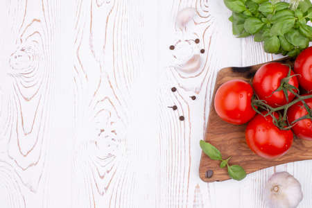 Top view fresh basil, garlic and tomatoes on a rustic white table, flat lay, copy space