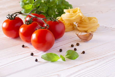Raw tagliatelle pasta with fresh basil, garlic and tomatoes on a rustic white table, Copy space.