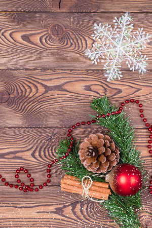 Christmas and New Year holiday background. Decor with fir branches, cones, Christmas decorations, beads, snowflakes, cinnamon sticks on a wooden table. Top view, empty space