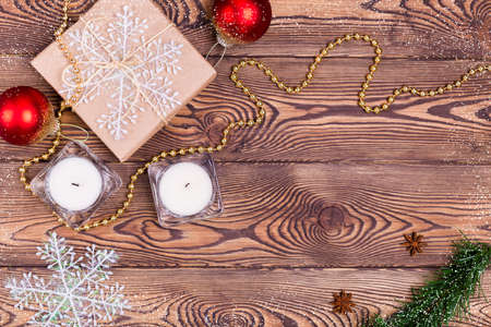 Christmas and New Year holiday background. Decor with gifts wrapped in kraft paper, candles, Christmas decorations, beads, snowflakes, on a wooden table. Flat lay, empty space Archivio Fotografico